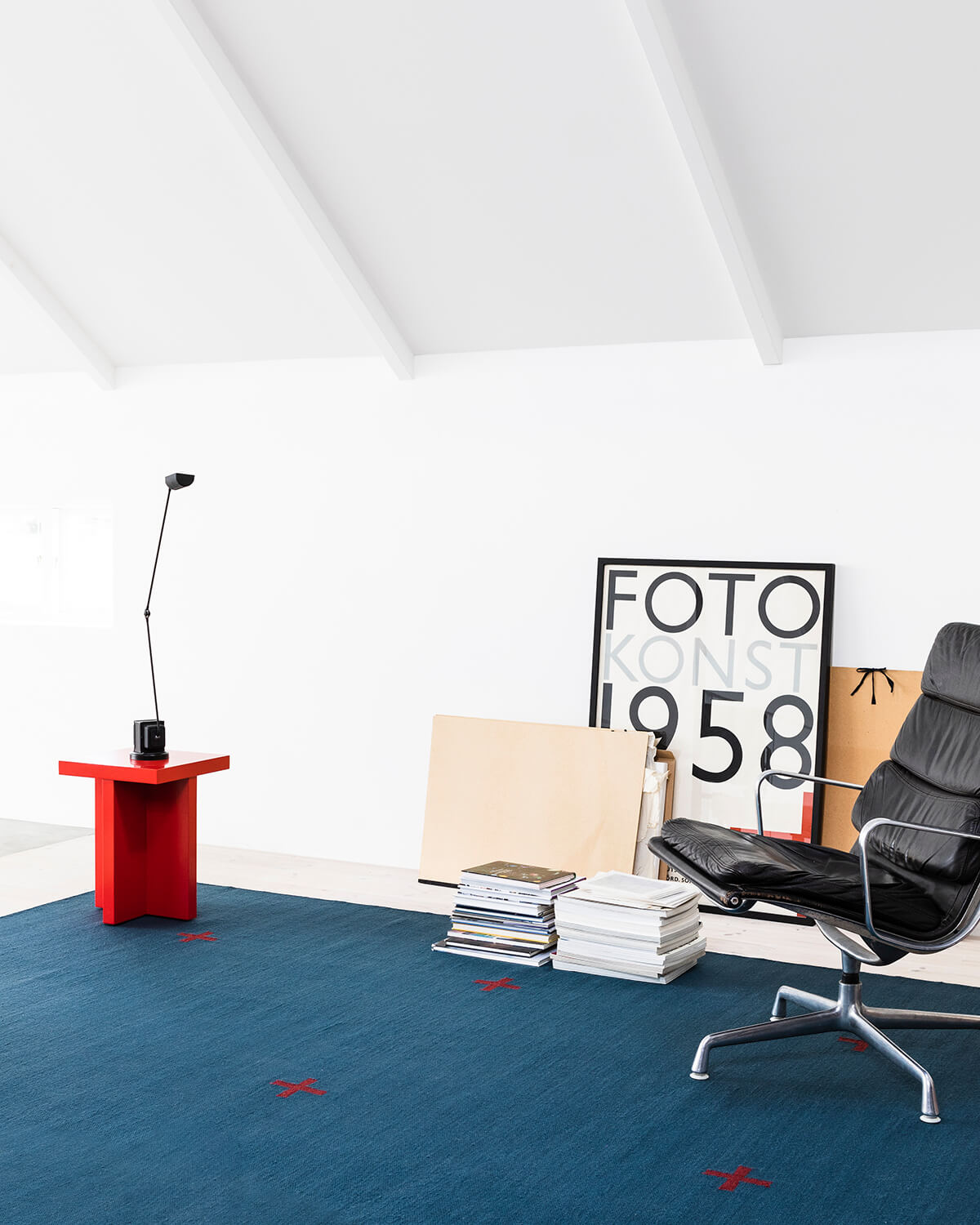 Plus in Blue displayed in a bright room with a leather chair.