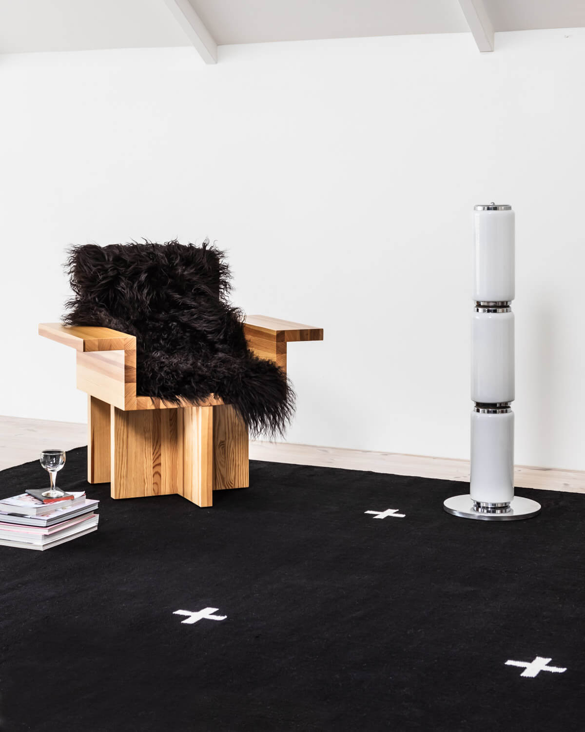 Plus rug in Black displayed together with a sculptural wooden armchair.