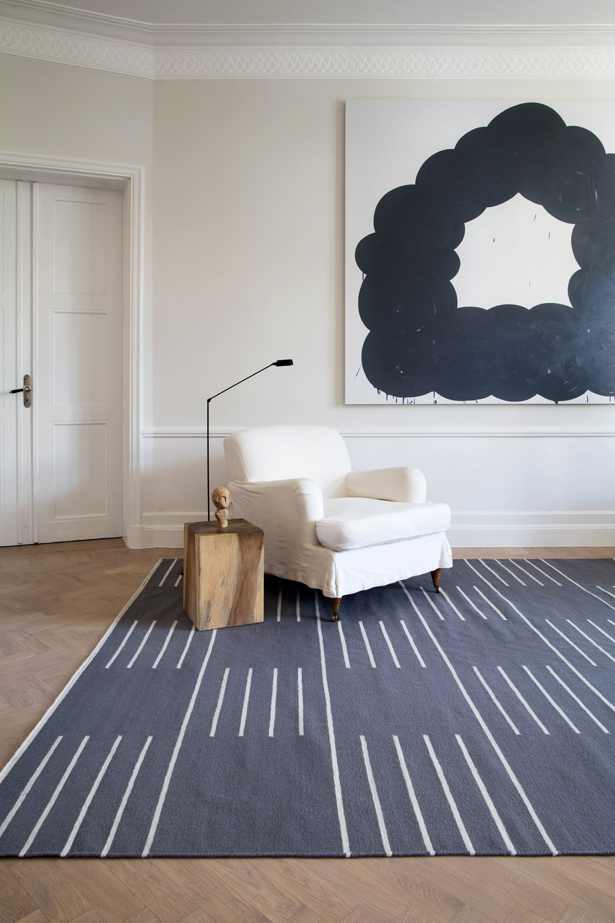 Stripes in color Gray displayed in a bright, sunny living room decorated with a white armchair.