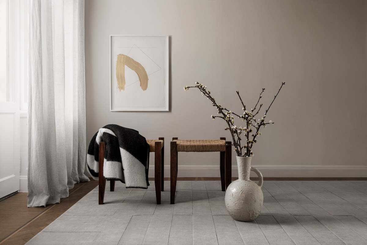 The Lux 2 rug in the color Oatmeal in a in a bright and beautiful apartment . Displayed with apple blossoms and two wooden stools.