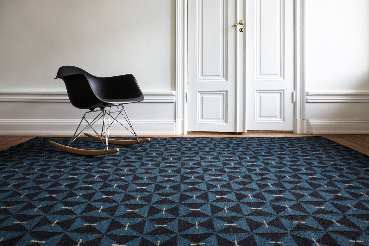 Mosaik in color Teal shown in an open room with a modern black rocking chair.
