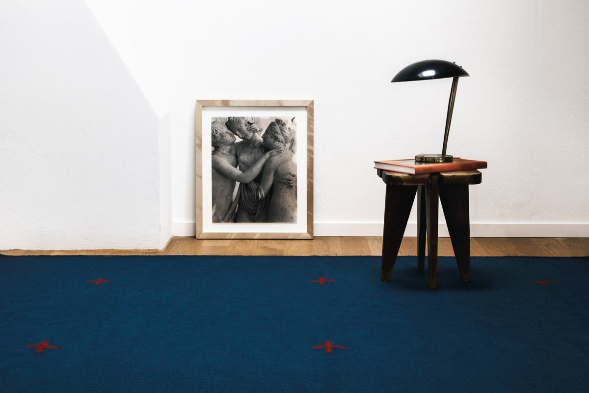 Flatweave rug Plus in Blue styled with a single frame and a small stool.