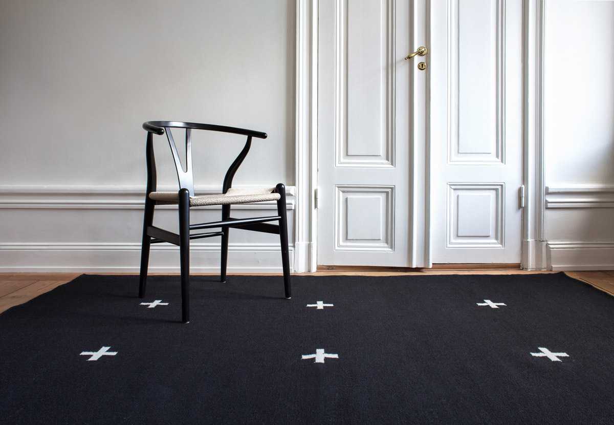Plus in Black shown in a sunny room with a single black chair.