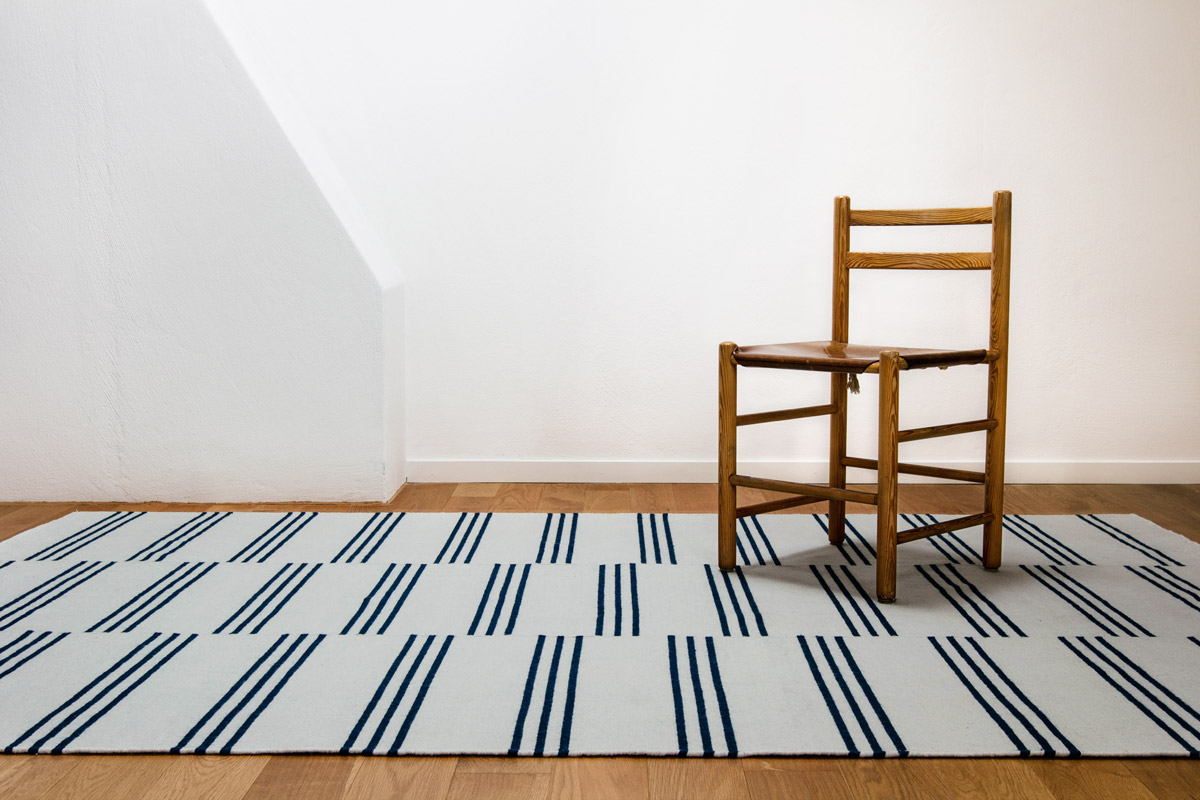 Stripes Blue styled with a single wooden chair.