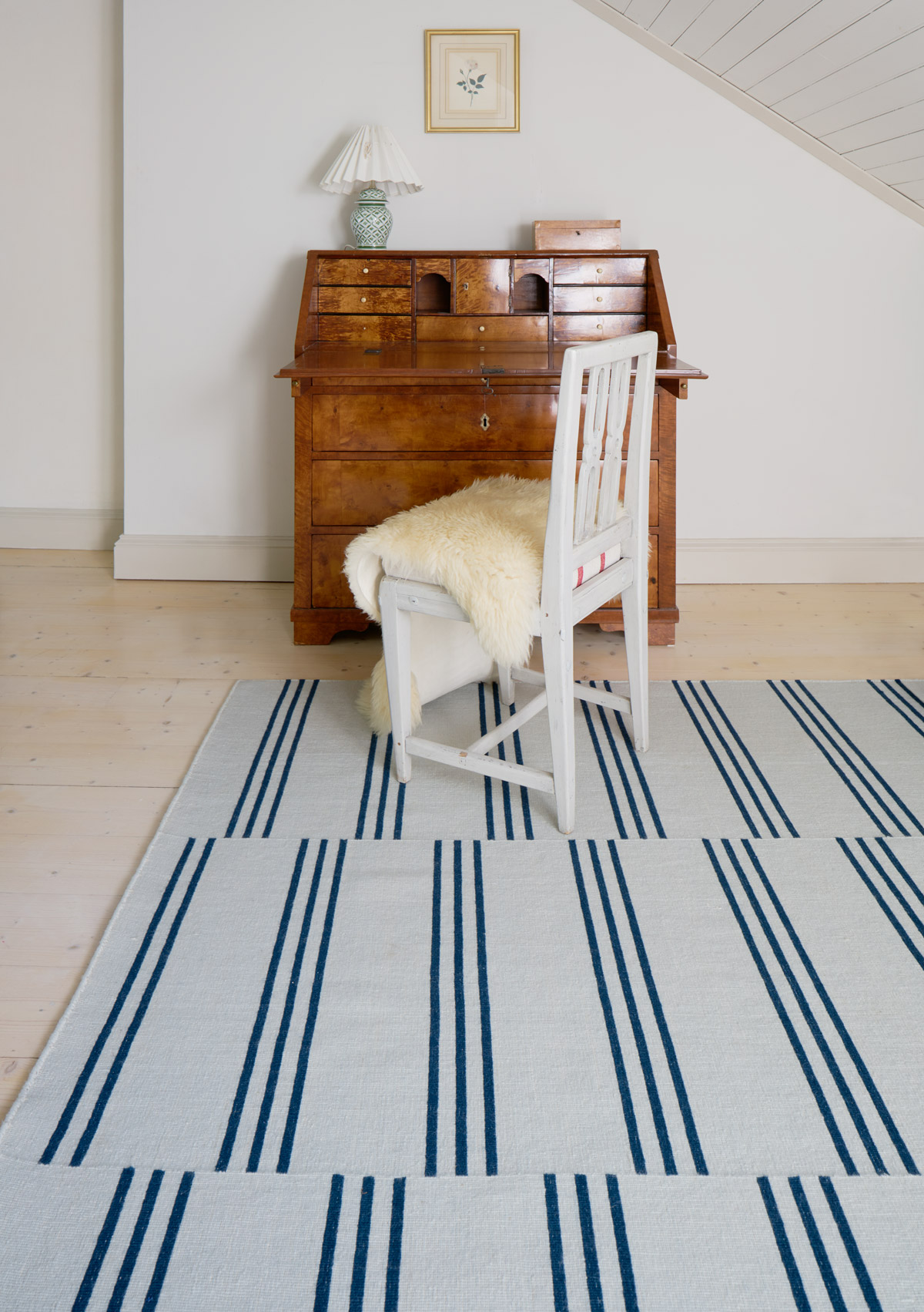 Stripes in Blue shown in a white room with a wooden desk and white chair.