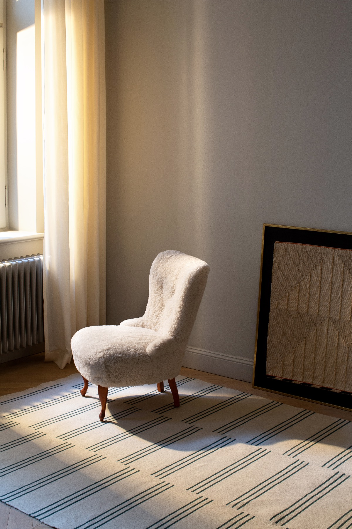 A green Stripes is laying in a sunny room with a white sheep fur armchair.