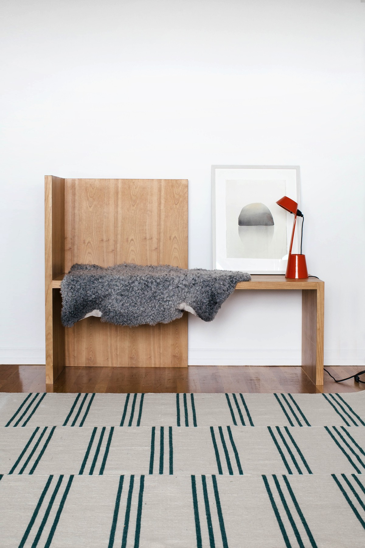 Stripes in Green shown in a white room with a wooden bench behind it.