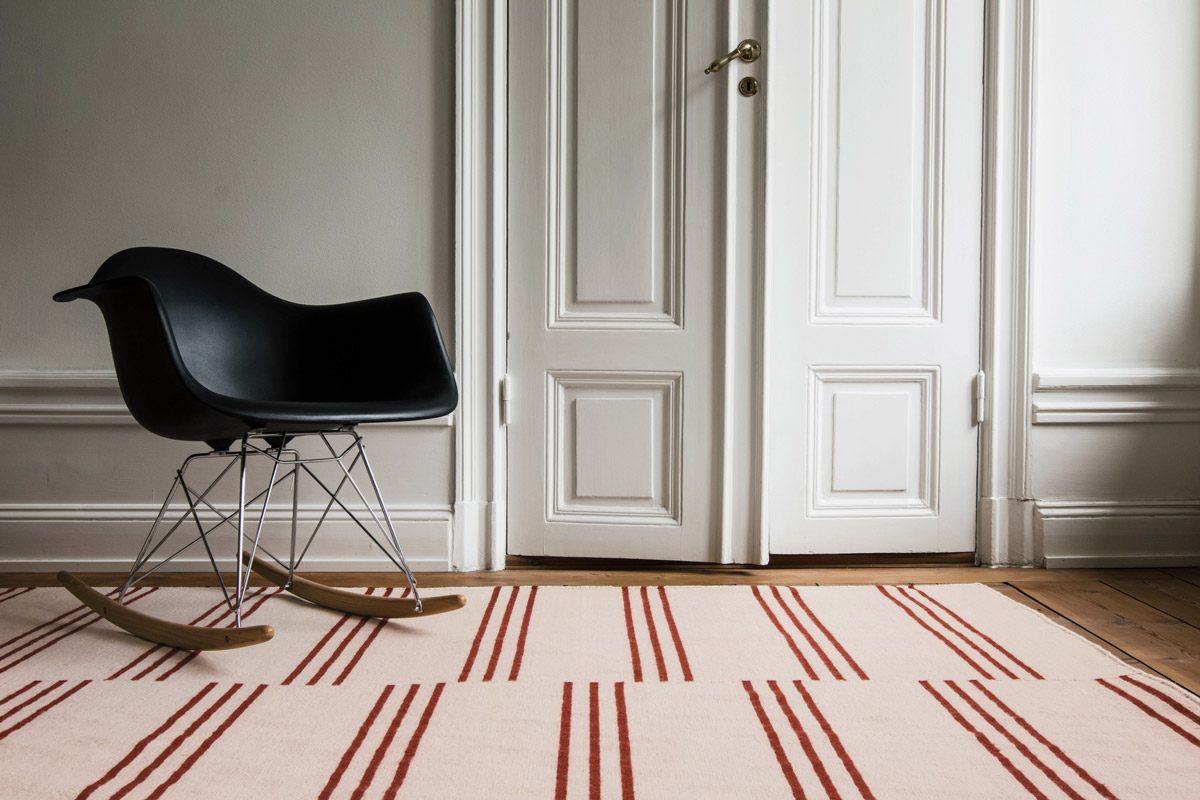 Stripes in Pink and red shown in an open room with a modern black rocking chair.