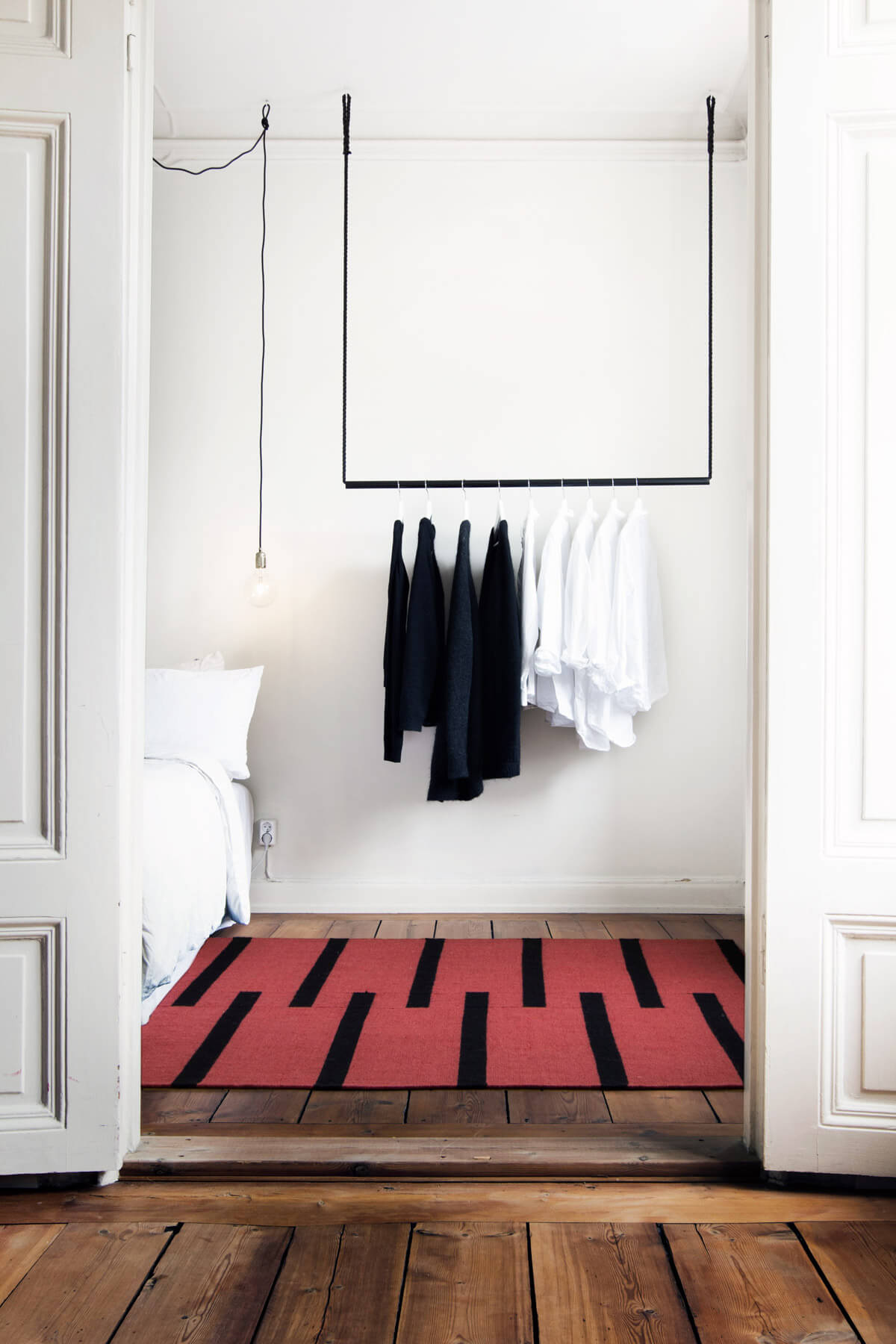 Flatweave rug Tiger in red displayed in a white turn of the century bedroom.