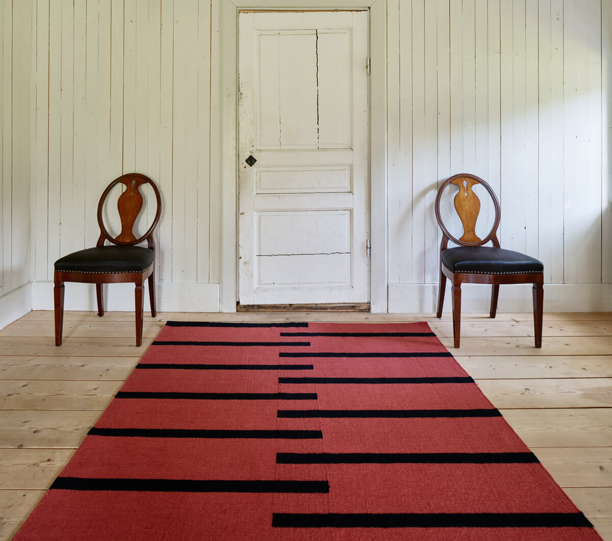 Flatweave Tiger in color red in a rustic, sunny room styled with two wooden chairs.