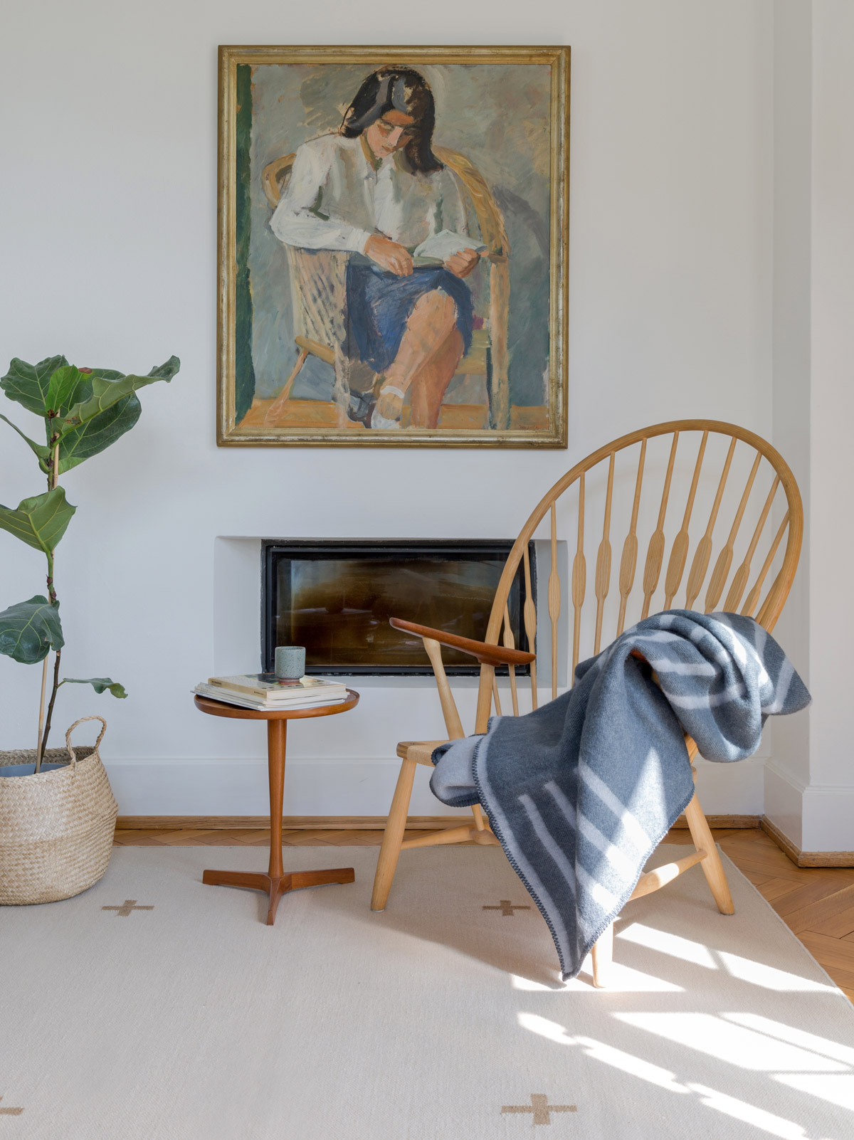 Wool blanket Classic in Steel Blue hung over a wooden armchair in a cosy living room setting.