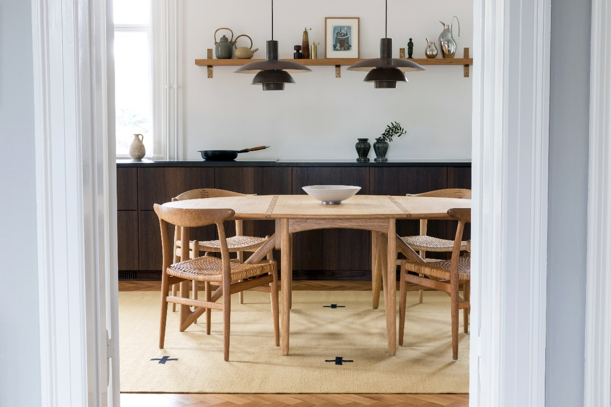Plus rug in color Mustard displayed in a sunny kitchen with beautiful wooden chairs and table on top..