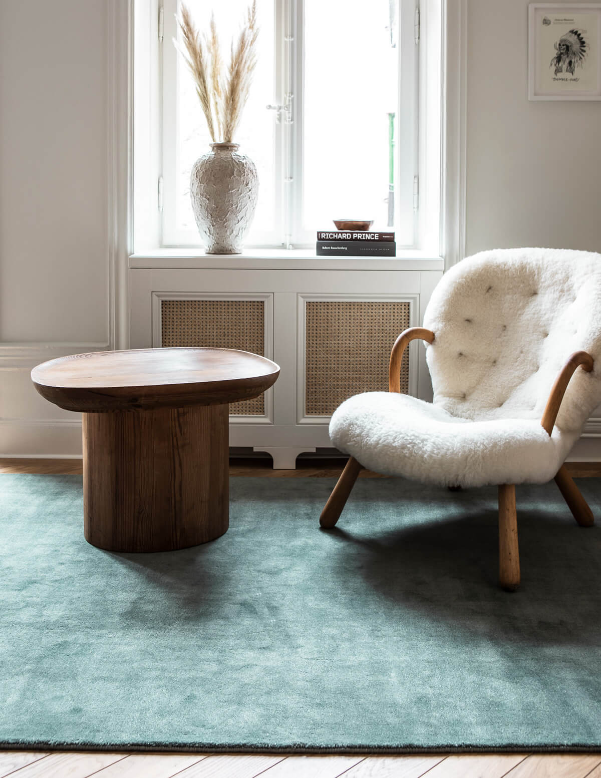 Grand in the color Pale Green displayed in a living room, styled with a wooden side table and sheep fur armchair.
