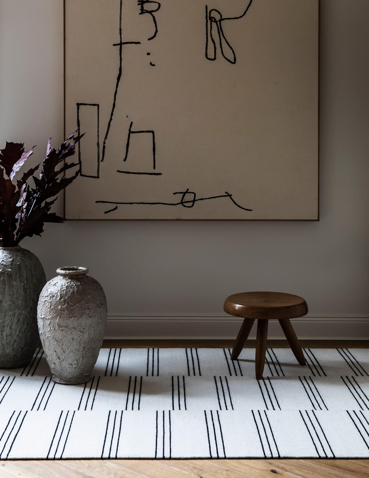 Flatweave rug Stripes in color Cream and Black styled with a small wooden stool and two large urns.