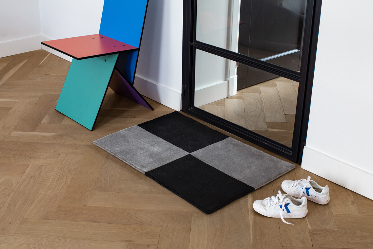 Plush door mat in color Gray and Black, displayed together with a pair fo sneakers and a colorful chair.