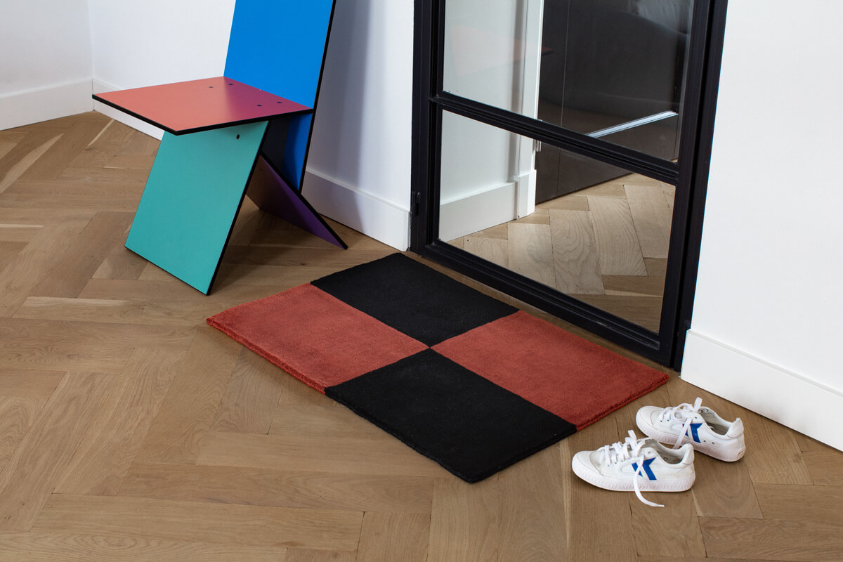 Plush door mat in color Red and Black, displayed together with a pair fo sneakers and a colorful chair.