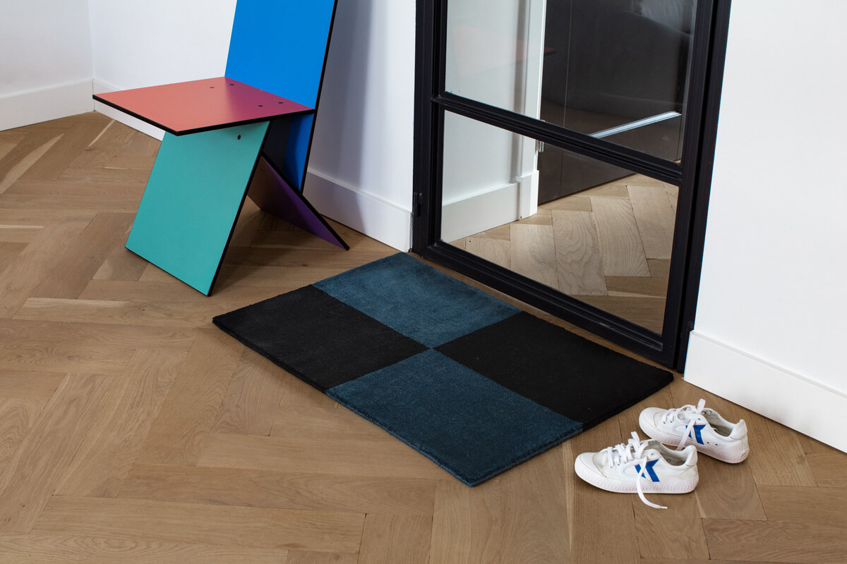 Plush door mat in color Teal and Black, displayed together with a pair fo sneakers and a colorful chair.