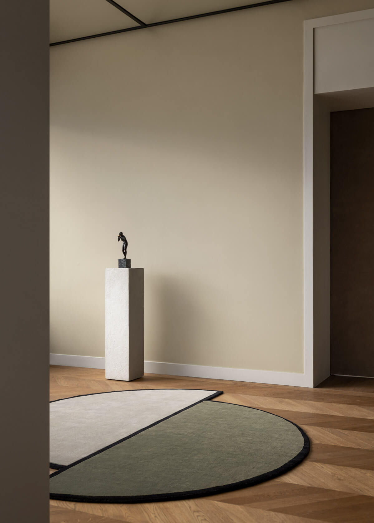 The rug AML 03 in a warm room with a sculpture on a pedestal in the back.,