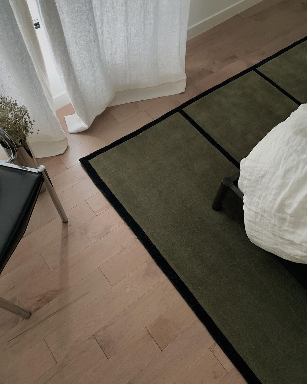 The corner of a AML 01 rug in Green and Black in a nice, modern bedroom.