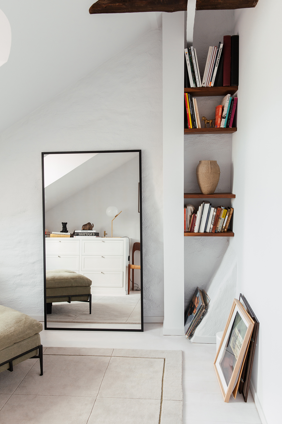 The AML 02 rug in Oatmeal and Green shown in a bright, modern apartment with a mirror and a bookcase.