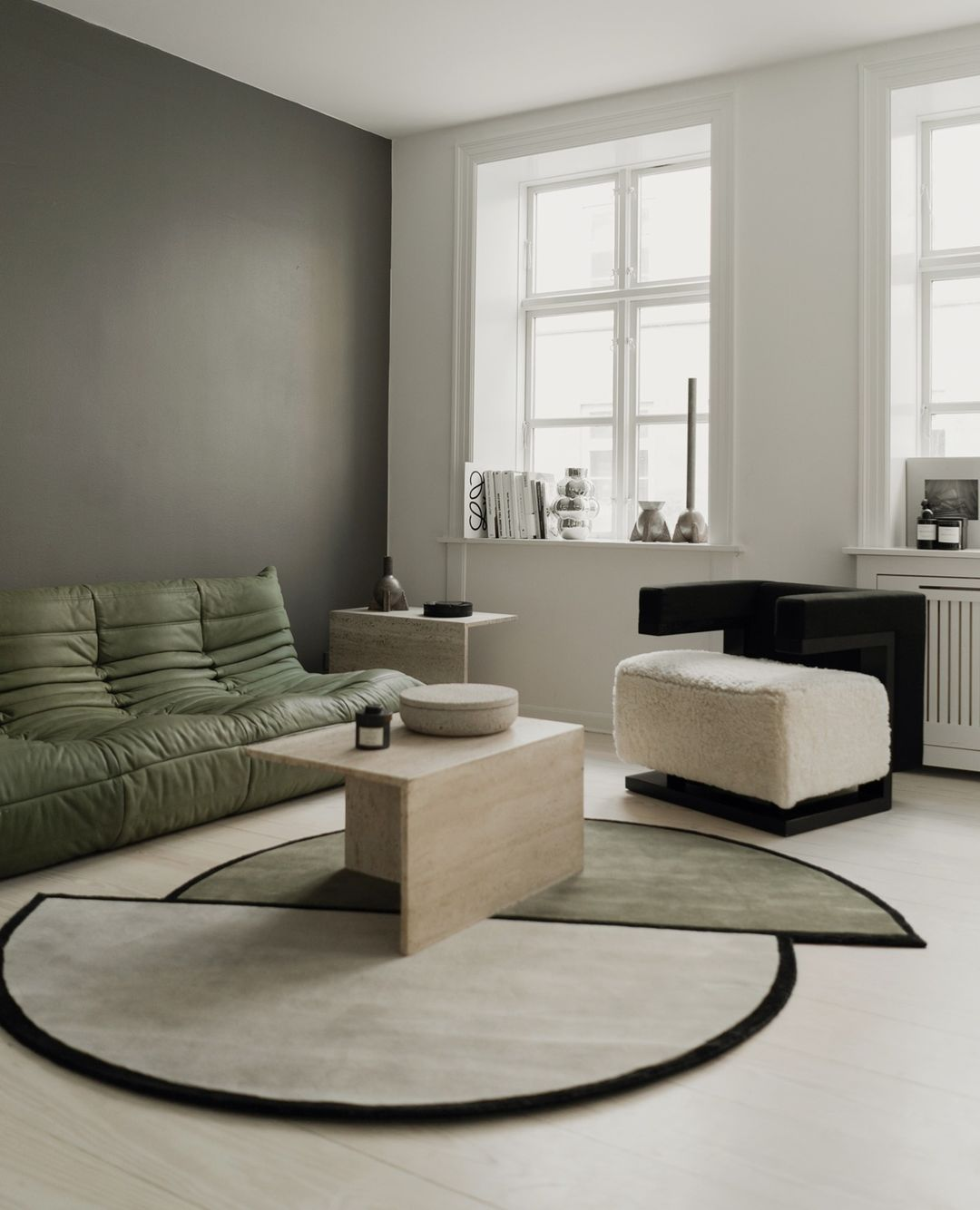 The AML 03 rug in contemporary apartment, shown with a green sofa and a black and white sheep fur armchair.