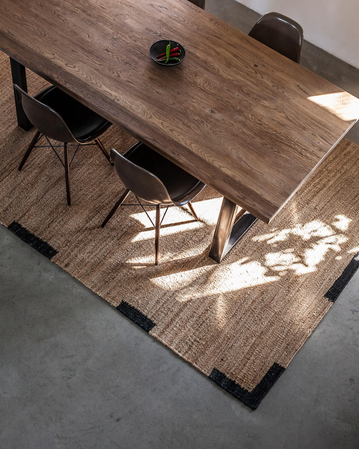 Birds eye view of Jute Edge in Black styled with a wooden dinner table and matching chairs.