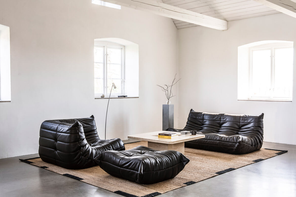 Jute Edge rug in black in a beautiful contemporary barn house displayed with a black, Toga, sofa group.