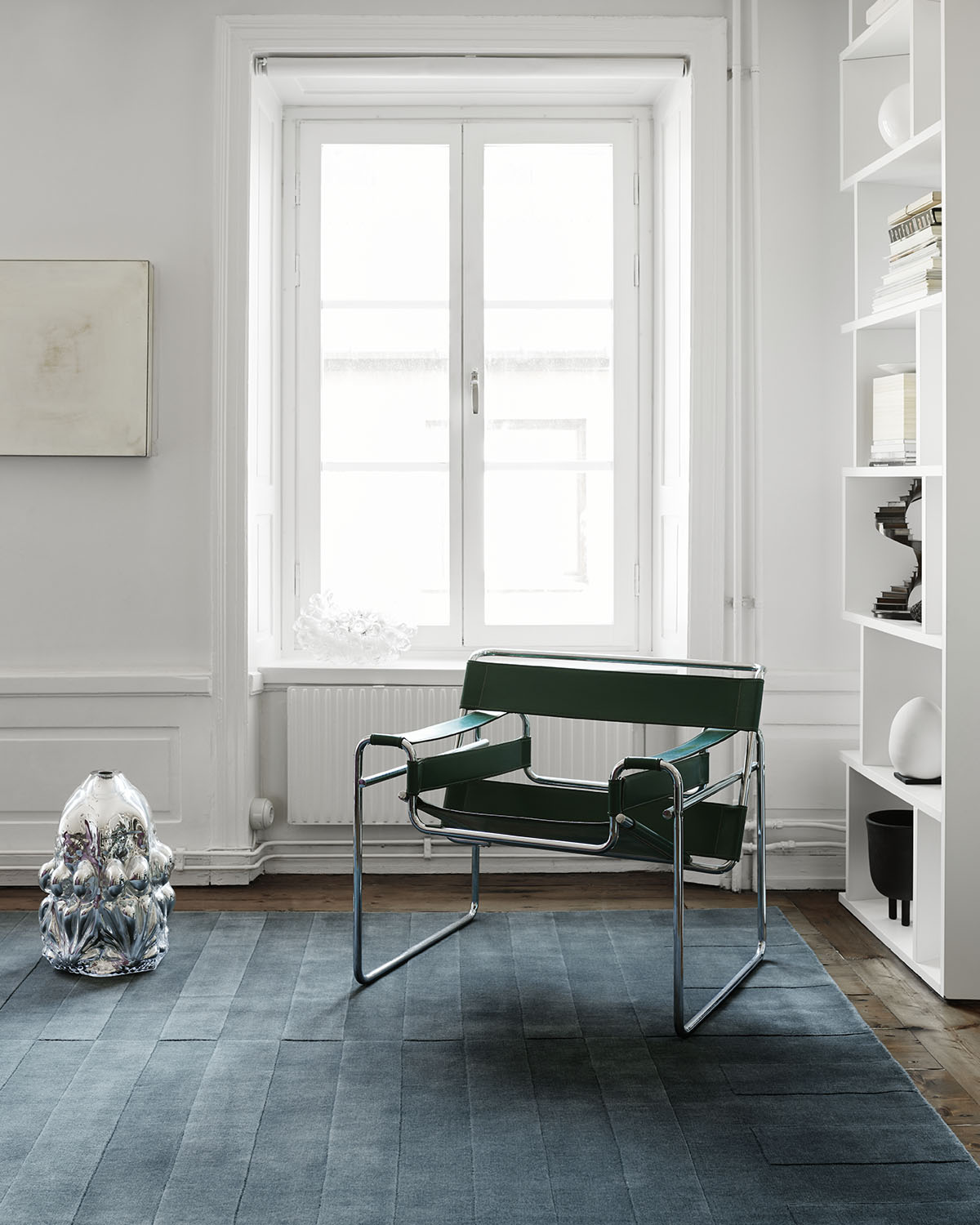 The plush rug Lux 2 in color Petrolium displayed in a light, white apartment with a classic leather and steel chair.