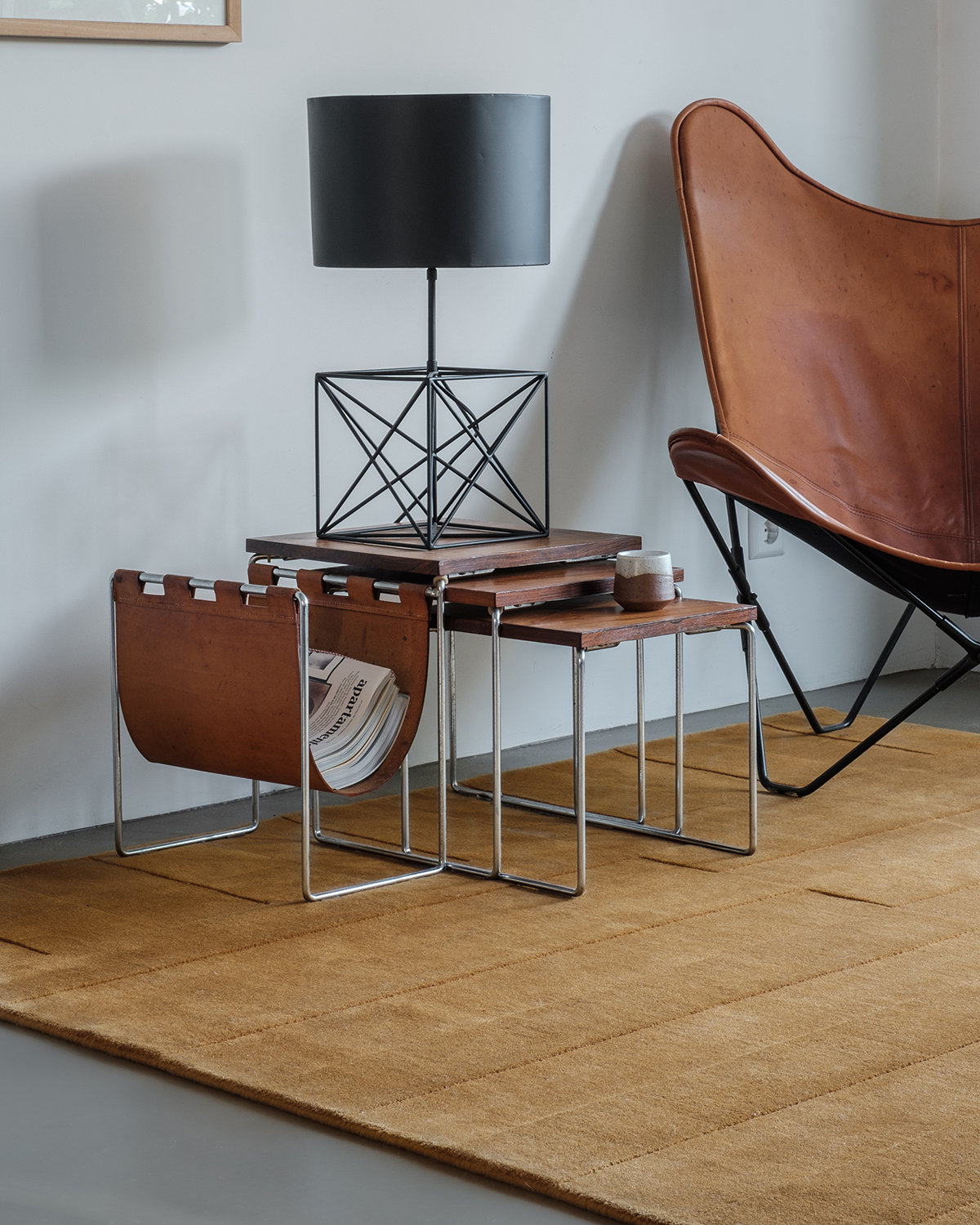 The Lux 2 in Leo shown in a living room together with a leather bar chair and a steel and wood side table.
