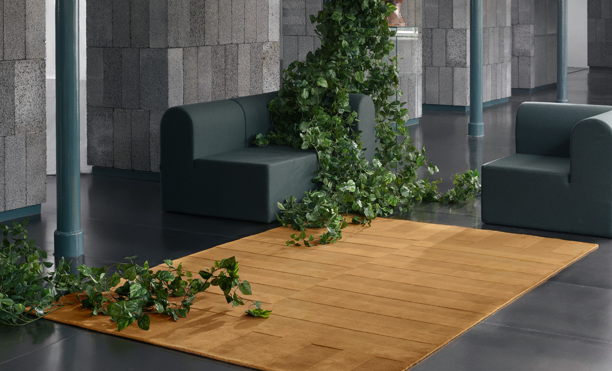Plush rug Lux 2 in the color Leo shown in a rustic room with a large green flower installment.