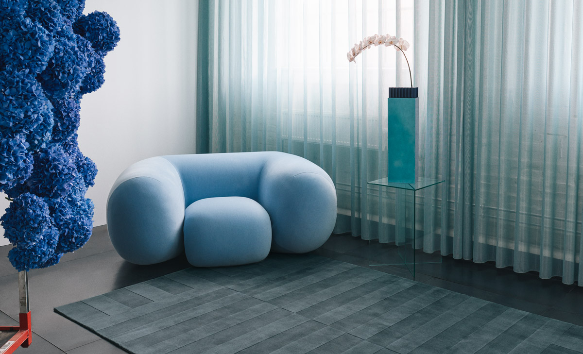 Lux 2 in the color Petroleum , shown in a gallery like setting together with a playful, big armchair in baby blue as well as blue hydrangeas.