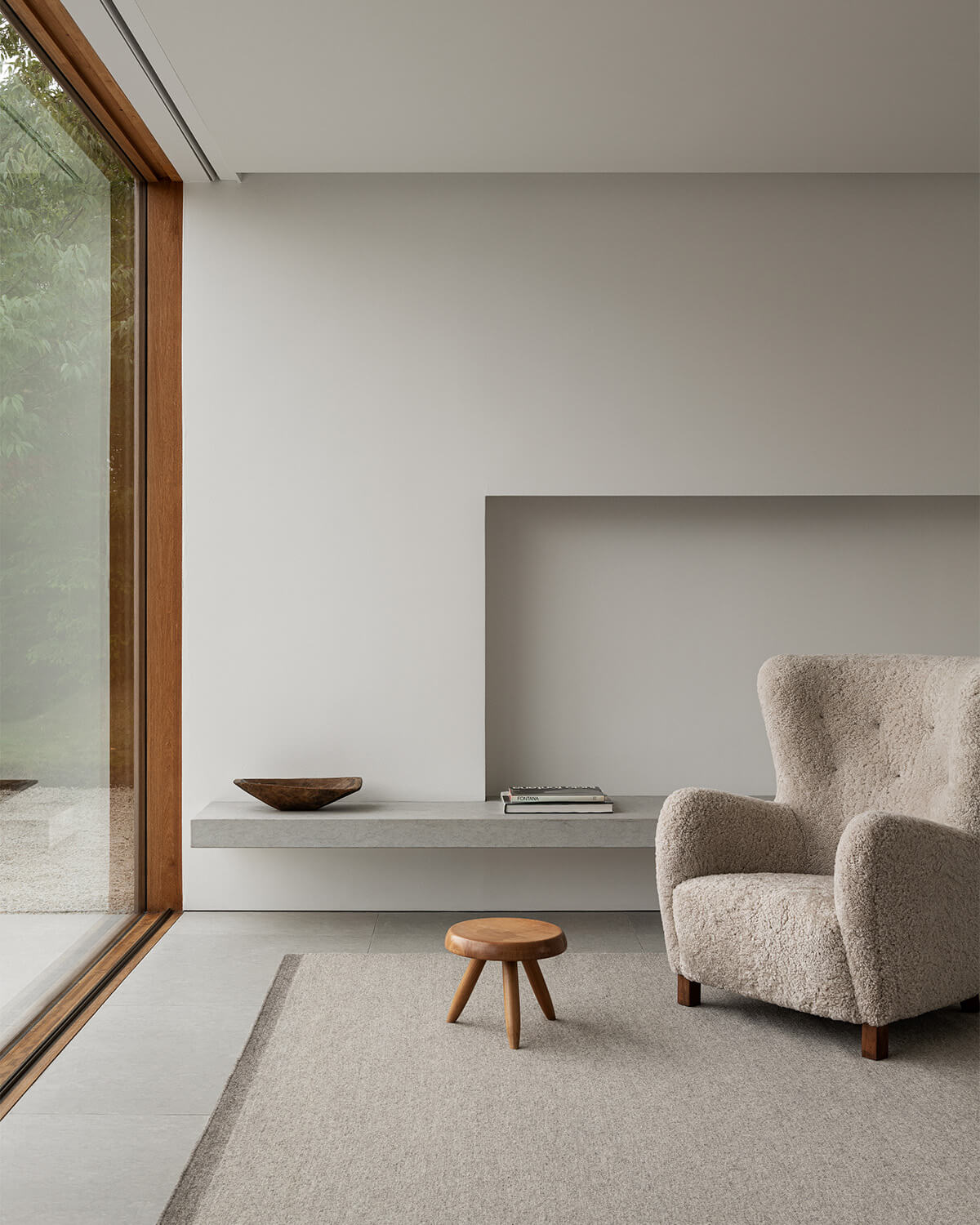 Zero in Warm Gray displayed in a contemporary and bright living room, styled with a white sheep fur armchair.