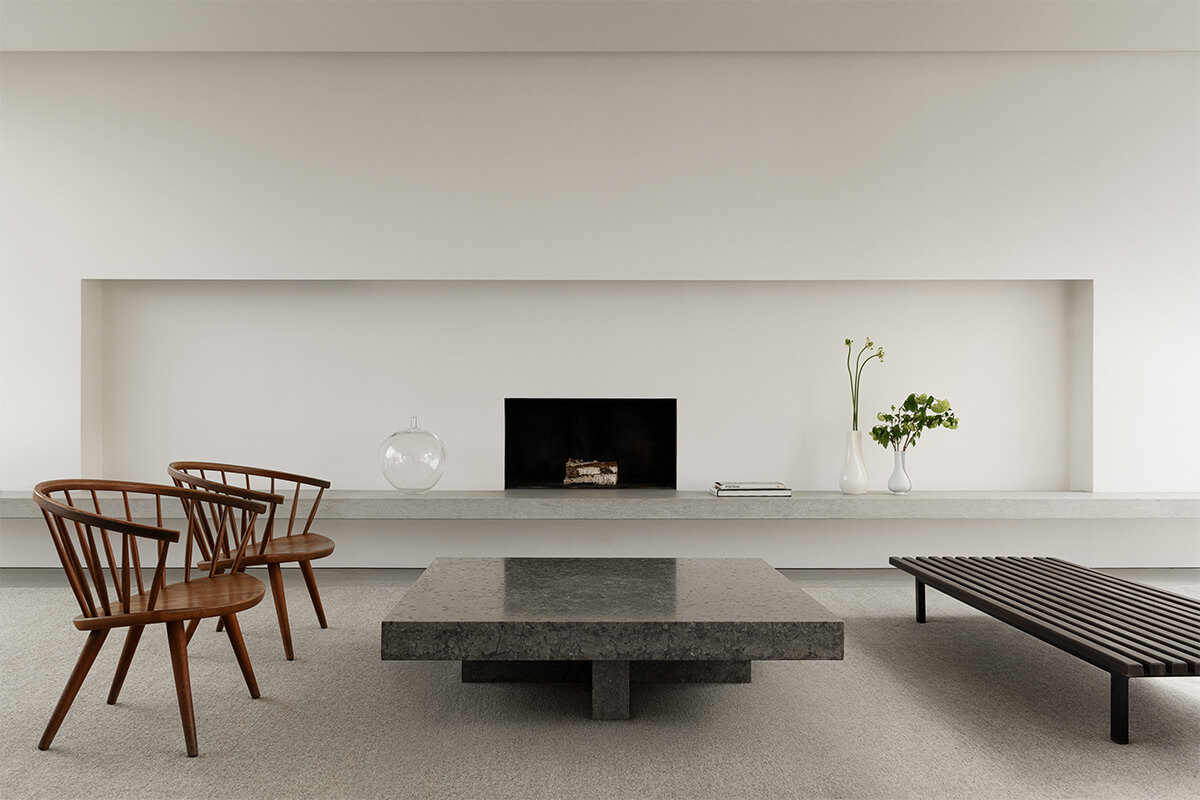 Flatweave rug Zero in color Warm Gray displayed in a contemporary living room, styled with a stone table and wooden furniture.