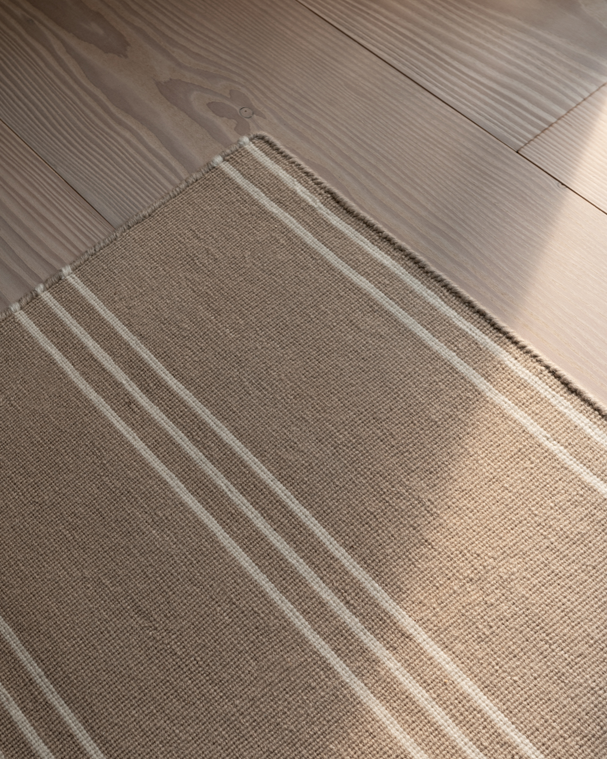 Close up off the corner on a Stripes rug in Sand / Cream.