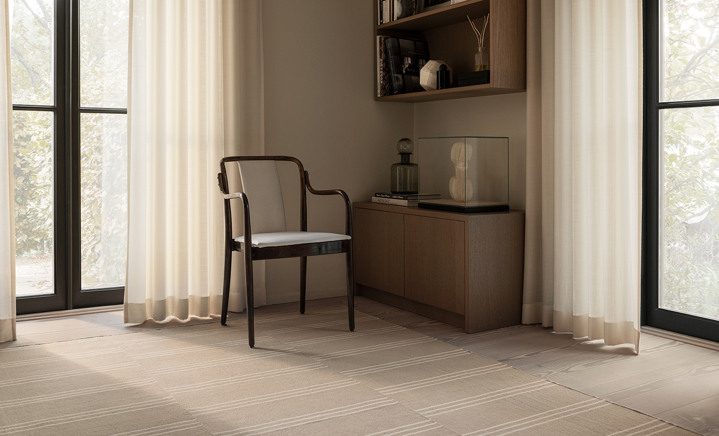 The Stripes flatweave rug in the colors Sand and Cream in a bright, beautiful room with white curtains.