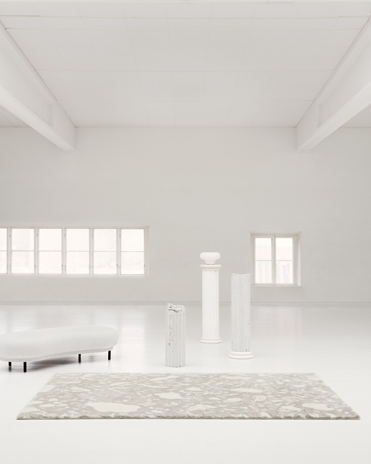 The shaggy Archipelago rug in Oatmeal in a white, contemporary setting with a rounded bench as well as some pillars.