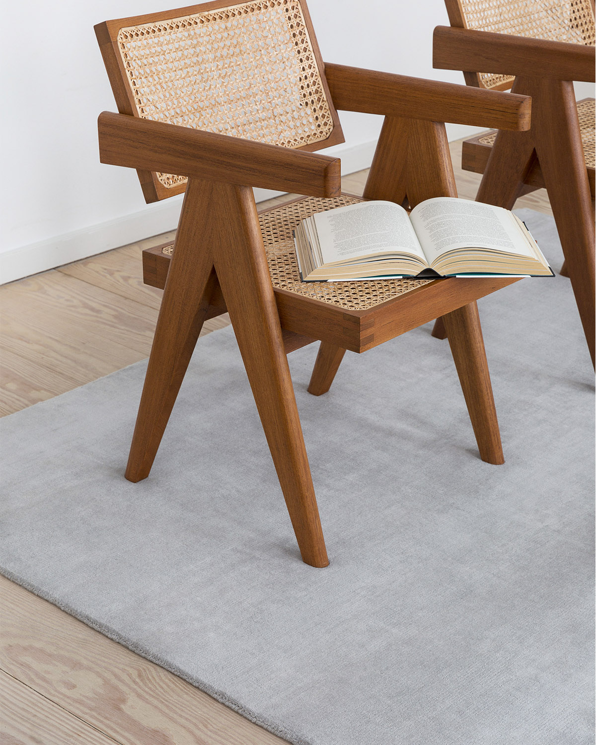 The rug Grand in Silver displayed in a living room together with wood and rattan armchairs.