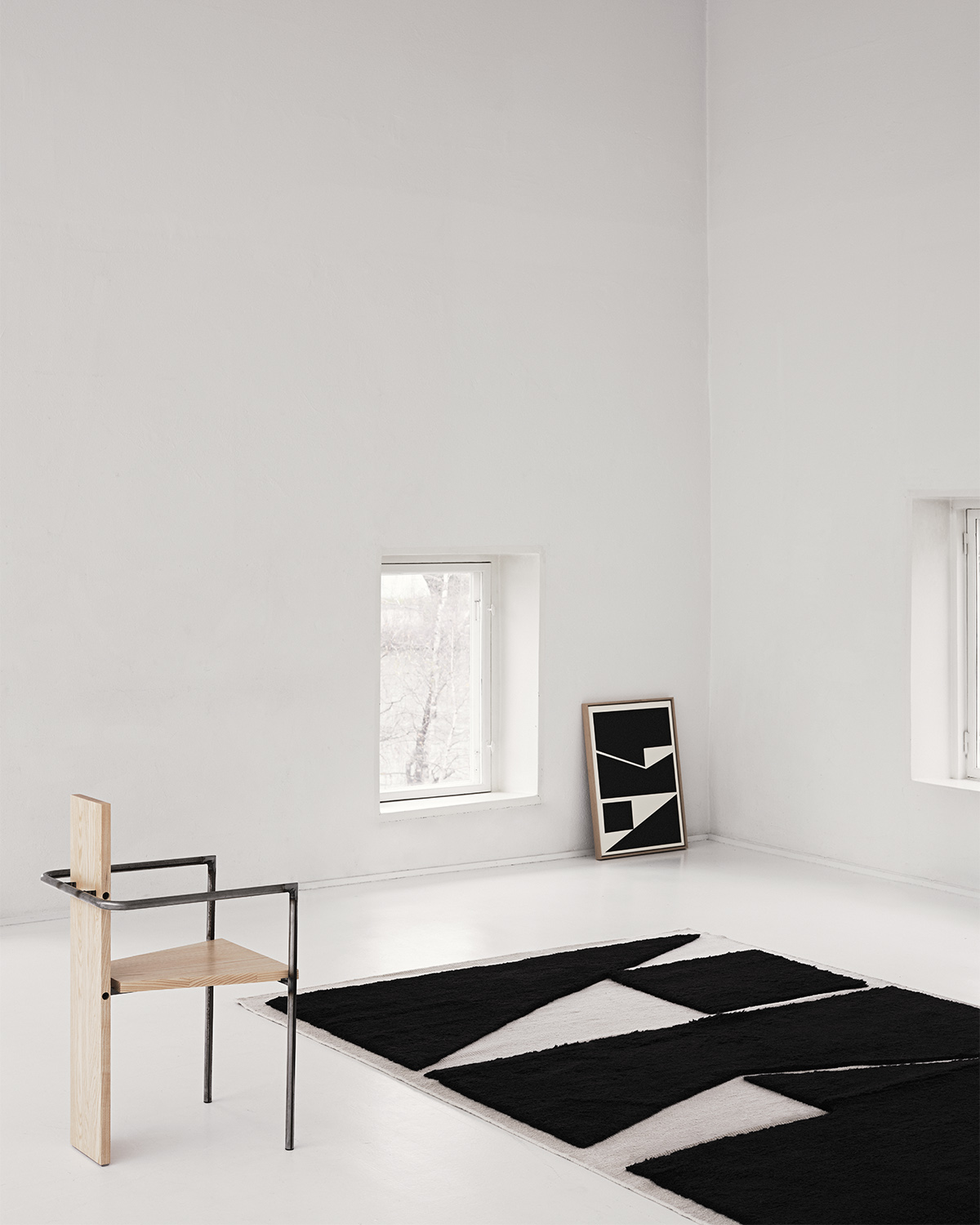The Untitled 1 rug in Black and Dusty White displayed in a contemporary, white space shown with the artwork that inspired it as well as a design chair.