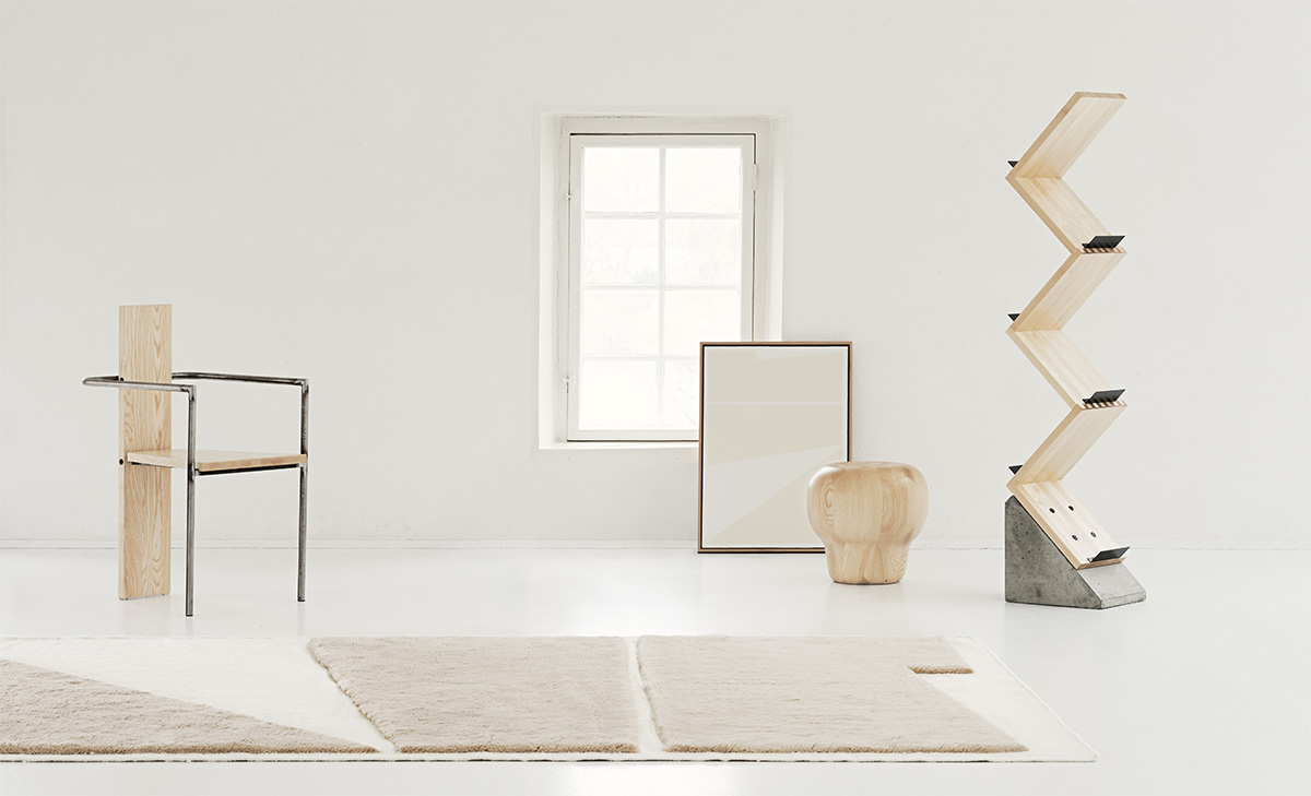 The Untitled 2 rug in Almond and Cream displayed in a white, gallery-like setting together with the artwork that inspired it as well as wooden design furniture.
