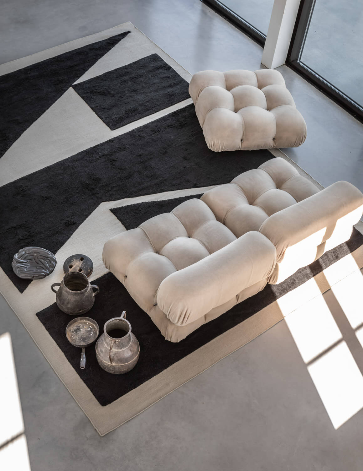 Untitled 1 in Dusty White and Black shown from above together with a beige sofa.