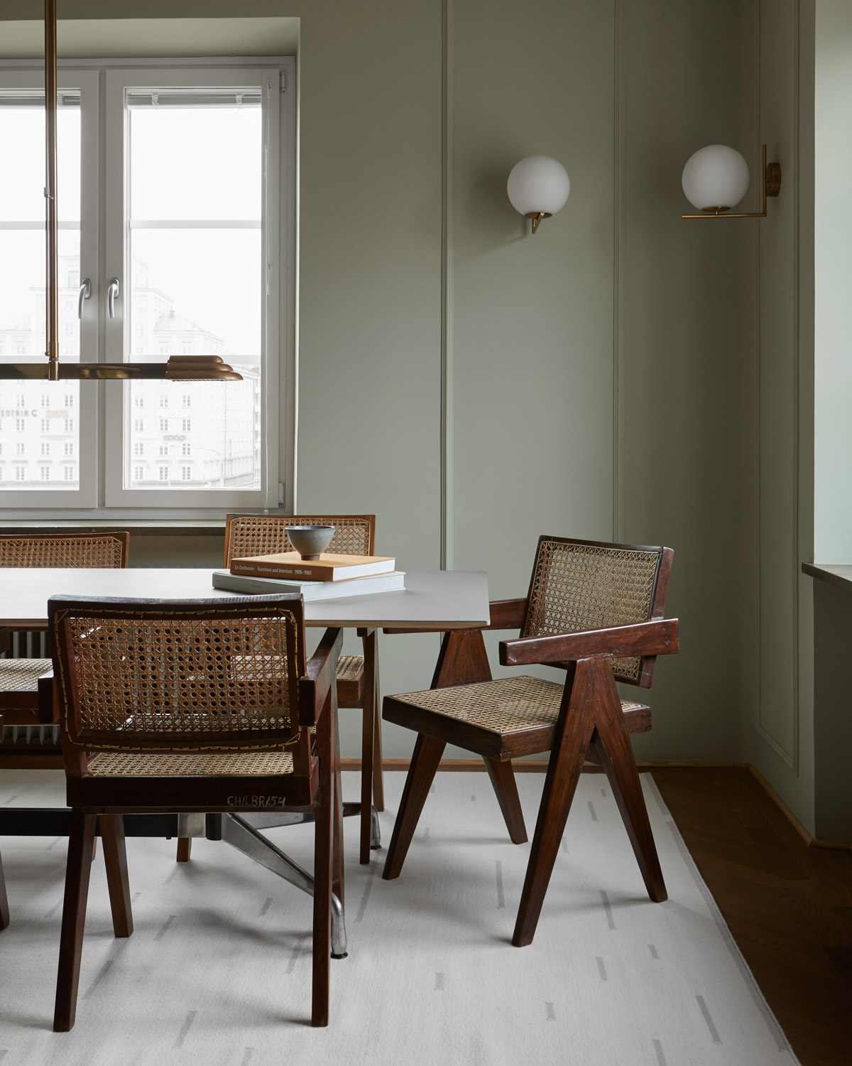 The Rain flat-weave rug in Dusty White in dining-room with vintage designer chairs