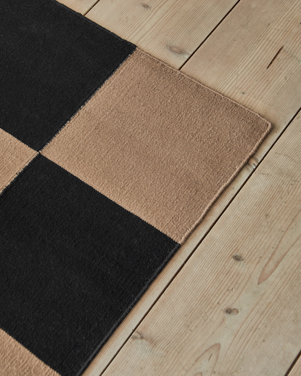 Close up of the tobacco/black Square rug