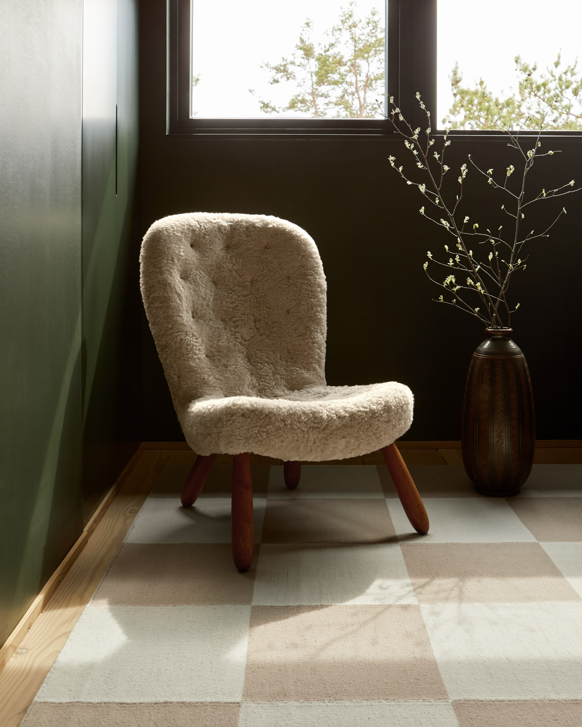 The Square sand flatweave rug photographed with a beautiful white chair.