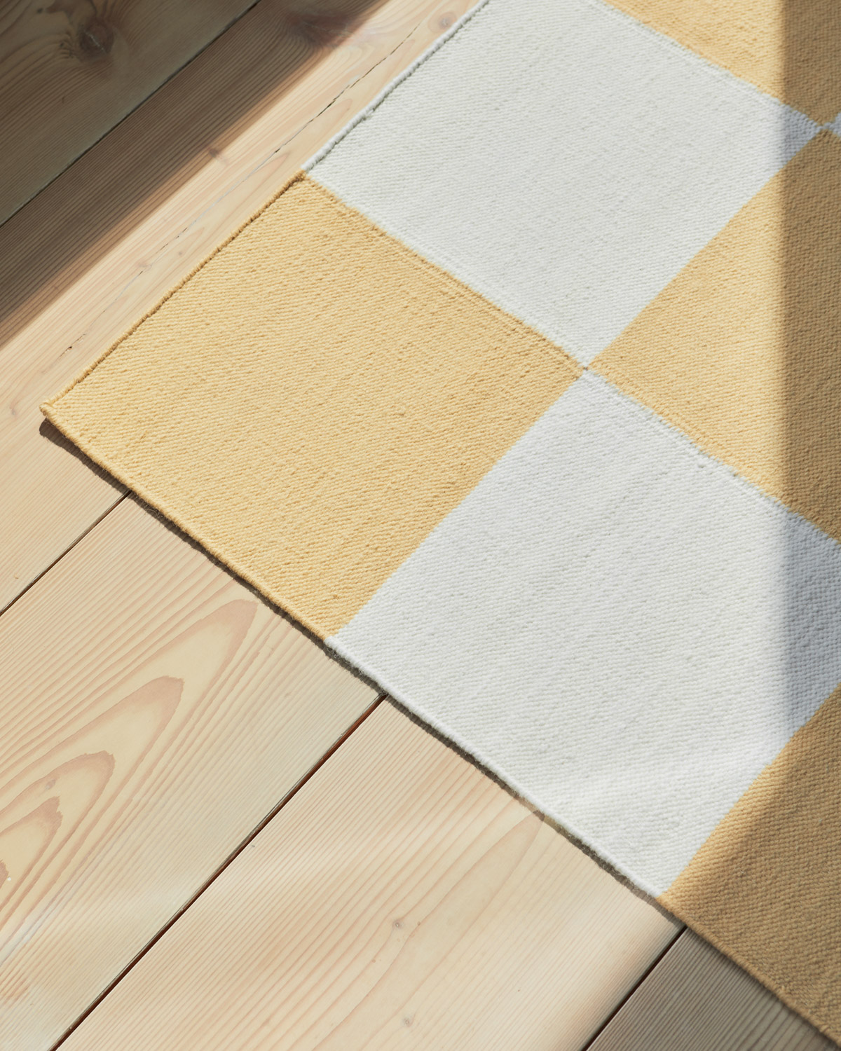 Close up of the yellow square flatweave rug