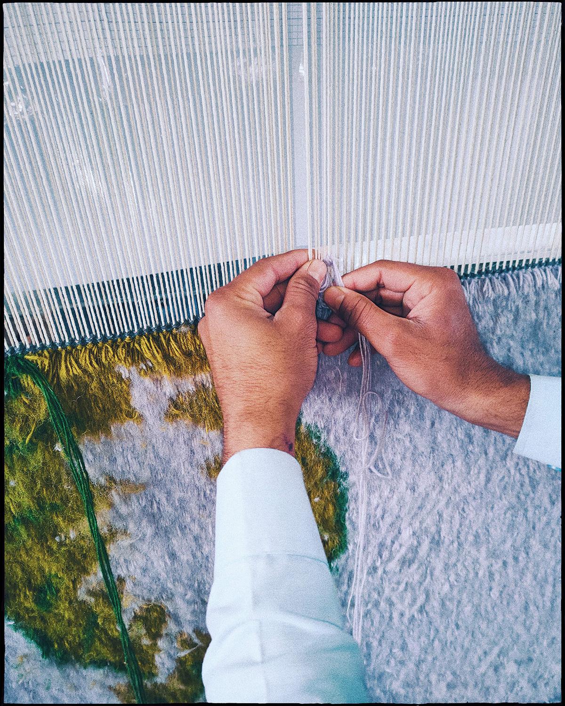 Close up of hands weaving a Climbing Vine-rug.